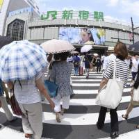 Shoppers cross a street in the Shinjuku district in Tokyo on Thursday, in intense summer heat. A heat wave this year has brought unprecedented scorching temperatures across many parts of Japan.   KYODO