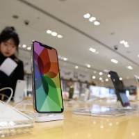 Apple iPhones are displayed at a SoftBank store in Tokyo. The Fair Trade Commission believes iPhone contracts in Japan may constitute a violation of antitrust regulations. | BLOOMBERG