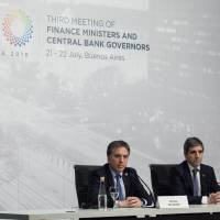 Luis Caputo (right), president of the Argentine central bank, and Argentine Treasury Minister Nicolas Dujovne, listen to a question at a news conference during the Group of 20 finance ministers and central bankers' meetings in Buenos Aires on Sunday. | BLOOMBERG