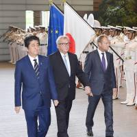 Prime Minister Shinzo Abe walks alongside European Commission President Jean-Claude Juncker (center) and European Council President Donald Tusk at the Prime Minister's Office in Tokyo on Tuesday. | KYODO