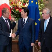 Prime Minister Shinzo Abe shakes hands with European Council President Donald Tusk as European Commission President Jean-Claude Juncker looks on before signing a free trade pact in Tokyo on Tuesday. | AP
