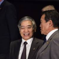 Bank of Japan Gov. Haruhiko Kuroda (left) chats with Finance Minister Taro Aso, who also holds the deputy prime minister portfolio, while attending the Group of 20 meetings of finance ministers and central bankers in Buenos Aires on Saturday. | BLOOMBERG