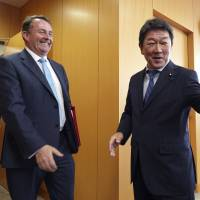 British Secretary of State for International Trade Liam Fox is greeted by economic revitalization minister Toshimitsu Motegi before their meeting in Tokyo on Tuesday. | AP