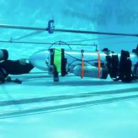 A device by Elon Musk's SpaceX and The Boring Company, designed to help rescue the remaining members of a soccer team trapped in a flooded cave in Chiang Rai, Thailand, is being tested in a swimming pool in Los Angeles in this still image taken from an undated video obtained from social media. | TWITTER @ELONMUSK / VIA REUTERS