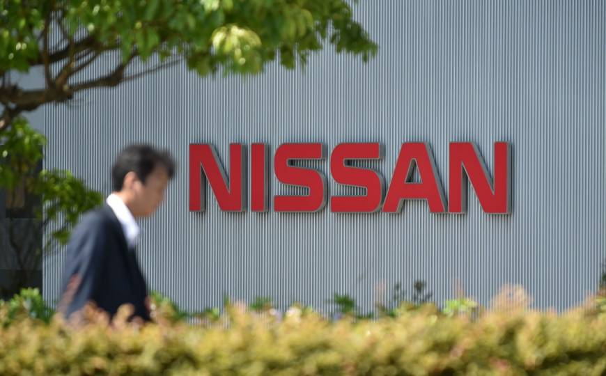 A man walks in front of the Nissan Motor Co. logo at its global headquarters in Yokohama, on May 11, 2017. | AFP-JIJI