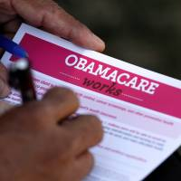 A man fills out an information card during an Affordable Care Act outreach event hosted by Planned Parenthood for the Latino community in Los Angeles in 2013. | REUTERS