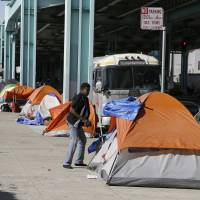 A man stands outside his tent on Division Street in San Francisco in 2016. San Francisco voters will decide in November whether to tax large businesses to pay for homeless and housing services in a city struggling with income inequality. | AP
