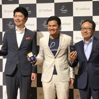 Handy Japan CEO Hironori Katsuse (left), Handy Japan founder Terence Kwok (center) and SoftBank Corp. CEO Ken Miyauchi pose for photos in Tokyo on Monday. | KAZUAKI NAGATA