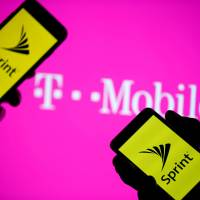 Smartphones with Sprint logo are seen in front of a screen projection of T-mobile logo, in this picture illustration taken April 30. | DADO RUVIC/ILLUSTRATION / FILE PHOTO GLOBAL BUSINESS WEEK AHEAD / VIA REUTERS