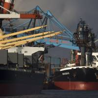 Bulk carrier ships sit moored at the Nippon Steel & Sumitomo Metal Corp. plant in Kashima, Ibaraki Prefecture, on April 18. Japan reported a current account surplus of ¥1.94 trillion in May, but in several areas growth in imports exceeded that of exports. | BLOOMBERG