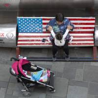 A woman tends to a child near a promotional gimmick in the form of a bomb and the U.S. flag outside a U.S. apparel shop in Beijing in April. | AP