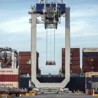 A ship to shore crane prepares to load a 40-foot shipping container onto a containership at the Port of Savannah in Savannah, Georgia, July 5. China's options to retaliate in an escalating trade dispute with Washington go beyond matching U.S. tariff hikes to targeting American companies and government debt. Its state-dominated economy gives regulators tools to hamper sales of engineering, shipping and other services — an area in which the United States runs a trade surplus — and to disrupt operations for automakers, restaurant chains and other American businesses in China. | AP
