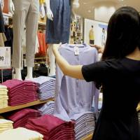A woman holds up a garment at a Uniqlo store in Ikebukuro, Tokyo, in April. | KYODO