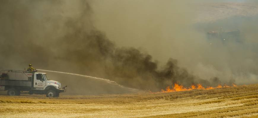 A truck and firefighters from Joint Fire District #2 work to put out a standing wheat and stubble fire just north of Walla Walla, Washington, Wednesday. The fire was started by combines harvesting wheat nearby. | GEG LEHMAN / WALLA WALLA UNION-BULLETIN / VIA AP