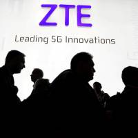 Visitors pass in front of the Chinese telecoms equipment group ZTE Corp. booth at the Mobile World Congress in Barcelona, Spain, in February. | REUTERS