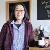 Bottom's up: Japanese winemaker Atsuko Radcliffe holds a bottle of her award-winning 2014 Shiraz at her vineyard, Small Forest. | KYODO