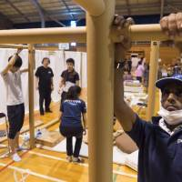 Peace Winds Japan volunteers install cardboard-based structures designed by architect Shigeru Ban at a gym converted into a shelter in Kurashiki, Okayama Prefecture.  | COURTESY OF PEACE WINDS JAPAN