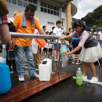 Local residents fill up water containers near a flooded area at Mihara No. 2 junior high school, which was acting as an emergency water supplying station, in Mihara, Hiroshima Prefecture, on Monday. | REUTERS