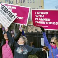 A Planned Parenthood supporter and opponent try to block each other's signs during a protest and counterprotest of abortion in St. Louis last year. | AP