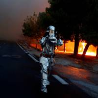 A firefighter wears a flame resistant uniform as a wildfire burns in the town of Rafina, near Athens, Monday. | REUTERS
