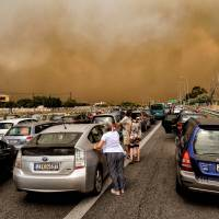 The National Road in Kineta, near Athens, is blocked by a wildfire on Monday. | AFP-JIJI