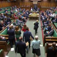 Copies of the Brexit white paper are brought into the chamber to be distributed to representatives while the U.K.'s Secretary of State for Exiting the European Union Dominic Raab speaks at the House of Commons in London on July 12, 2018, in this video still from footage broadcast by the UK Parliament's Parliamentary Recording Unit (PRU). | AFP-JIJI