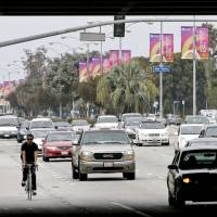 A bicyclist rides next to cars along Venice Boulevard under the 405 freeway overpass in Los Angeles, California, in 2010. California's Air Resources Board recently published an assessment showing the state had met an ambitious target, set in 2006, to cut greenhouse gas emissions to 1990 levels by 2020. | BLOOMBERG