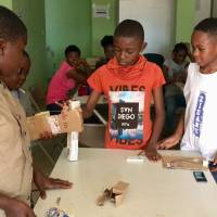 Children conduct an experiment using a model hand made out of cardboard and string at the NextGen Technology Center in Yaounde, Cameroon, on July 11. | THOMSON REUTERS FOUNDATION / INNA LAZAREVA