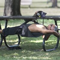 A man relaxes in Montreal park on Thursday amid a heat wave. | AP
