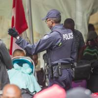 A Canadian police officer talks to migrants after they crossed the border illegally near Hemmingford, Quebec, on Monday. | AFP-JIJI