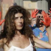 People with hands painted in red protest in front of the Italian Interior Ministry headquarters in Rome Wednesday. Dozens of protesters marched in front of the ministry to protest government's hard-line immigration policy. | AP