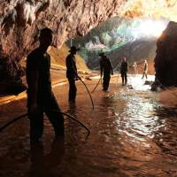 Thai rescue teams arrange a water pumping system at the entrance to a flooded cave complex where 12 boys and their soccer coach have been trapped since June 23, in Mae Sai, Chiang Rai province, northern Thailand, Saturday. | ROYAL THAI NAVY / VIA AP
