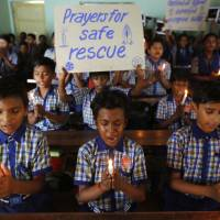 Students at a school in Ahmadabad, India, hold candles and pray for a group of Thai youth soccer players and their coach who have been trapped since June 23, in Mae Sai, Chiang Rai province, northern Thailand, Monday. | AP