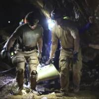 This undated photo from video released via the Thai Navy SEAL Facebook Page on Wednesday shows rescuers hold an evacuated boy inside the Tham Luang Nang Non cave in Mae Sai, Chiang Rai province, in northern Thailand. | THAI NAVY SEAL FACEBOOK PAGE / VIA AP