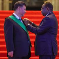 Chinese President Xi Jinping receives a decoration from Senegalese President Macky Sall at the Palace of the Republic in Dakar on Saturday. | AFP-JIJI