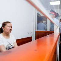 Sayragul Sauytbay, 41, an ethnic Kazakh Chinese national and former employee of the Chinese state who is accused of illegally crossing the border between the countries to join her family in Kazakhstan, sits inside a defendants' cage during a hearing at a court in the city of Zharkent on July 13, 2018. Secretive 'reeducation camps' that allegedly hold hundreds of thousands of people in a Muslim-majority region of western China have become the focus of a court case in Kazakhstan, which is also testing the country's ties with Beijing. | AFP-JIJI