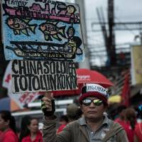 A protester holds a banner during the State of the Nation address by Philippine President Rodrigo Duterte, in Quezon City on July 23. | BLOOMBERG