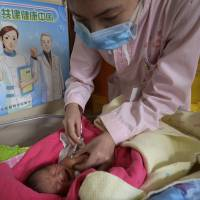 A baby receives a vaccine shot next to a poster that reads 'standardize vaccination and build a healthy China' at a hospital in Handan, in northern China's Hebei province, on April 25.   AP