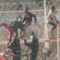 African migrants in this still image from video climb the border from Morocco to Spain's North African enclave of Ceuta Thursday. | FARO TV / REUTERS TV / VIA REUTERS