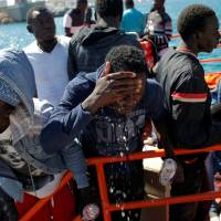 Migrants, intercepted aboard dinghies off the coast in the Strait of Gibraltar, cool off on a rescue boat as they wait to disembark after arriving at the port of Tarifa, southern Spain, Thursday. | REUTERS