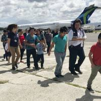 Families separated under President Donald Trump administration's zero tolerance policy return home to Guatemala City Tuesday after being deported from the United States. After lining up on the tarmac, they headed to a processing center where they were screened and given identification before being released back into the country. | AP