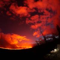 A U.S. Geological Survey geologist making observations of the fissure 8 lava channel near Kilauea volcano in Hawaii, is pictured through a fish-eye lens at sunset on July 3. | REUTERS