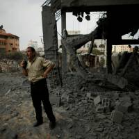 A Palestinian man looks at a building that was destroyed by Israeli airstrikes in Gaza City Sunday. | REUTERS