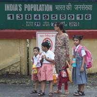 An Indian woman waits with children for their school bus in front of a national 'population clock' in Mumbai on Wednesday. | AFP-JIJI