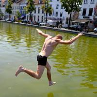 A man jumps into a canal at Sint-Katelijne-Sainte Catherine in Brussels on Thursday as temperatures rose above 33 degrees Celsius, the third day in a row with temperatures above 30. | AFP-JIJI