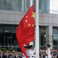 Hong Kong's guard of honor hoists a Chinese flag during a ceremony to mark the 21st anniversary of the Hong Kong handover to China in the city Sunday. | AP