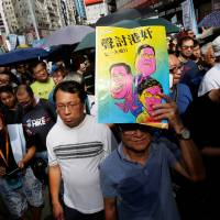 A protester carries a leaflet mocking top officials during a march in Hong Kong on Sunday to mark the 21st anniversary of the city's handover to Chinese sovereignty from British rule. | REUTERS