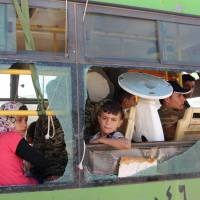 Evacuated Syrians from Fuaa and Kafraya in Idlib province are seen through a broken bus window during evacuating pro-regime fighters and inhabitants Thursday. Several thousand residents evacuated two pro-regime towns in northern Syria today putting an end to one of the longest sieges of the country's seven-year civil war. Fuaa and Kafraya are the last remaining areas under blockade in Syria and a rare example of pro-government towns surrounded by rebel forces. | AFP-JIJI