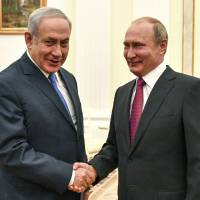 Russian President Vladimir Putin (right) greets Israeli Prime Minister Benjamin Netanyahu during their meeting at the Kremlin in Moscow Wednesday. | YURI KADOBNOV / POOL PHOTO / VIA AP
