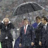 Russian President Vladimir Putin stands underneath an umbrella as FIFA President Gianni Infantino (left) covers his head during a rainstorm and French President Emmanuel Macron watches after the final match between France and Croatia at the 2018 soccer World Cup in Moscow on Sunday.   AP